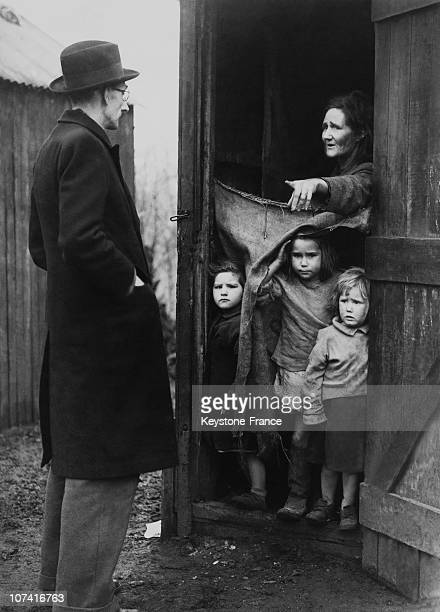 Authorities Visiting Mother And Six Children Leaving In Mud Hut In England On December 1946