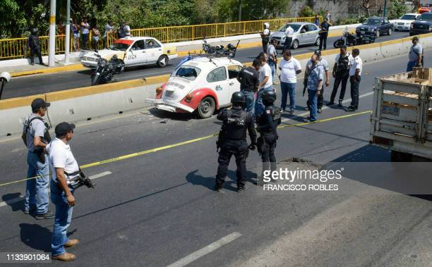 Authorities work at the scene where four racketeering suspects where shot down by security forces during a persecution and shootout along a highway...