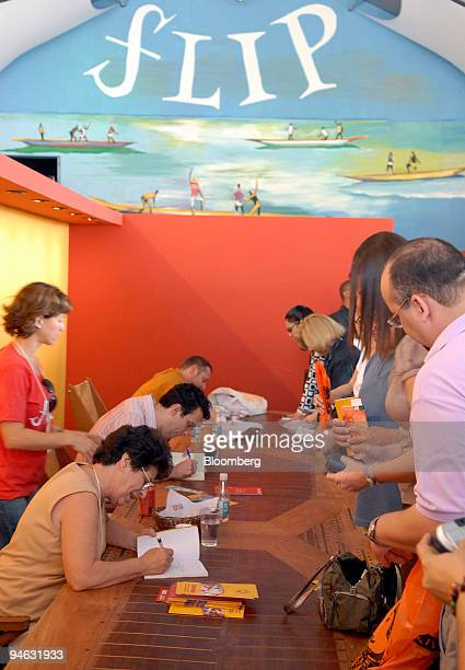 Authors Maria Valria Rezende Andr Laurentino and Juliano Garcia Pessanha sign books after a discussion panel inside the main tent during the Parati...