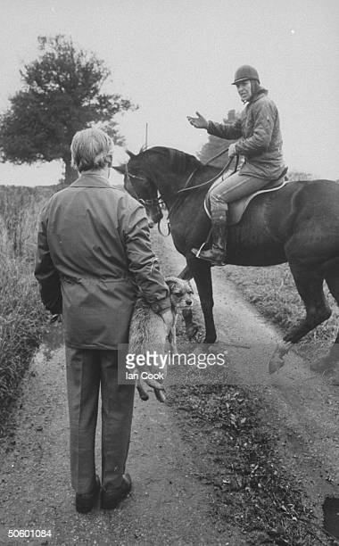 Author/veterinarian Dr. James Alfred Wight holding his border terrier dog under one arm as he chats w. Neighbor Penny Stevens, astride her English...