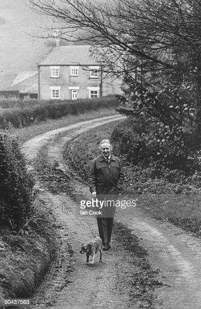 Author/veterinarian Dr. James Alfred Wight walking along dirt road w. His border terrier dog.