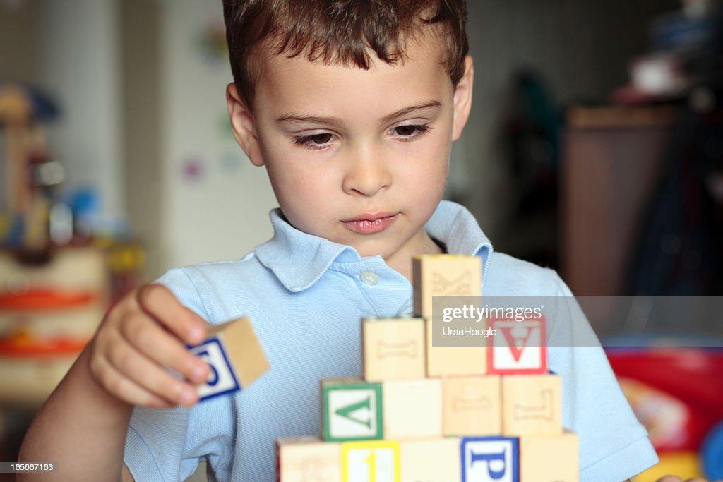 Autistic boy building with blocks : Stock Photo
