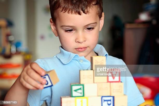 niño autista con bloques de construcción - autismo fotografías e imágenes de stock