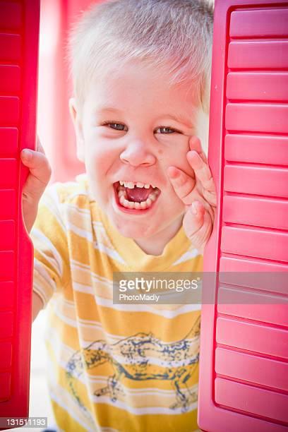Autistic boy peeks through red shutters