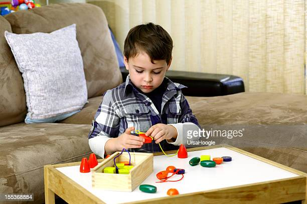 Autistic boy playing with colorful wooden beads