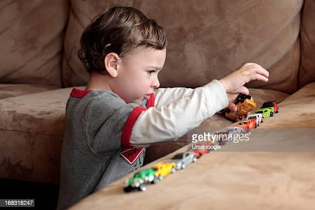 autista niño jugando con coches de juguete - autismo fotografías e imágenes de stock