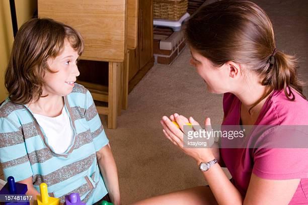 chica autista de recibir alabanzas durante la terapia - autismo fotografías e imágenes de stock