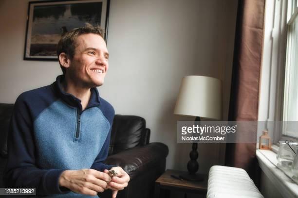 hombre trans autista en casa sonriendo mientras mira por la ventana - autismo fotografías e imágenes de stock