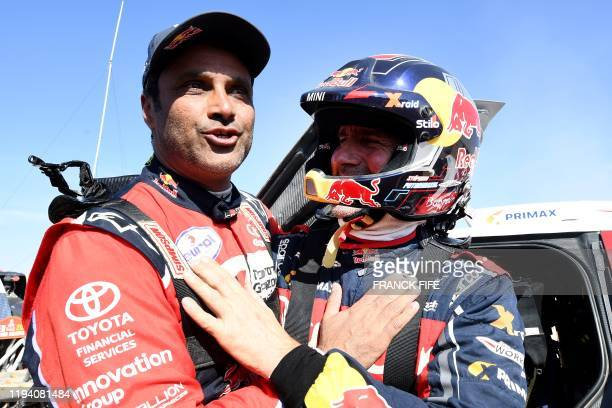 Auto category third-placed JCW X-RAID Mini Team France's Stephane Peterhansel speaks with second-placed Toyota's team Qatar's driver Nasser...