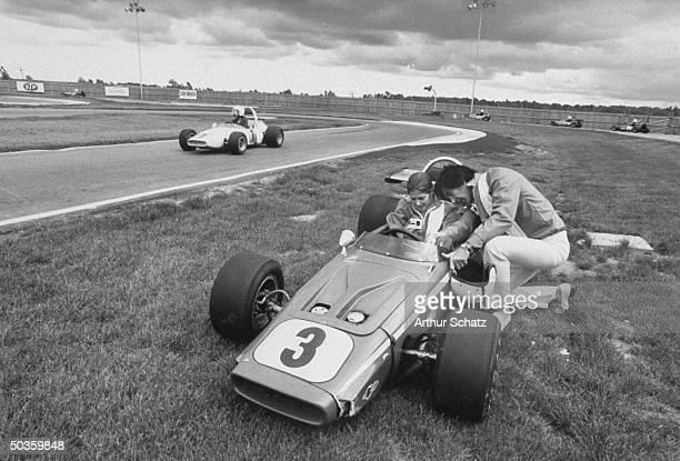 Auto designer John Z DeLorean teaching his wife Max Factor model Cristina Ferrare how to drive a stock car