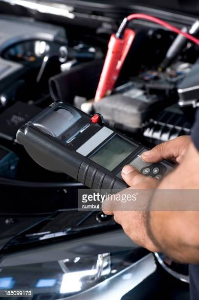 Auto mechanic checking car battery