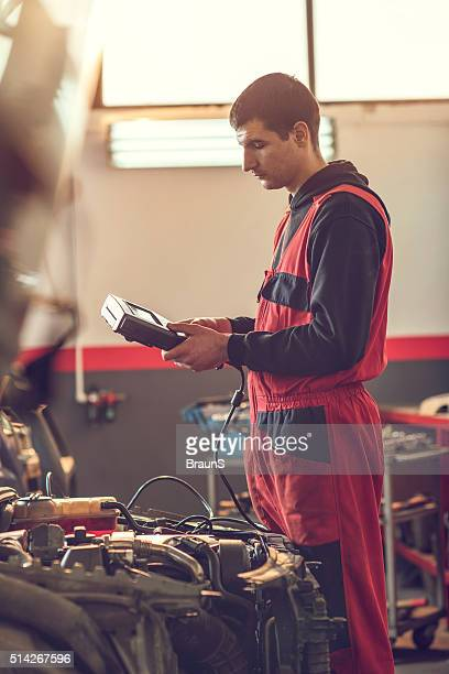 Auto mechanic examining a car engine with voltmeter.