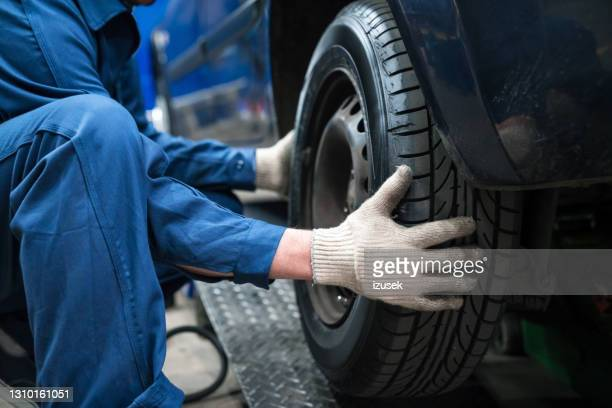 auto mechanic fixing wheel - glove stock pictures, royalty-free photos & images