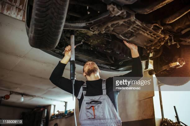 ガレージの自動車整備士 - 吊り上げる ストックフォトと画像