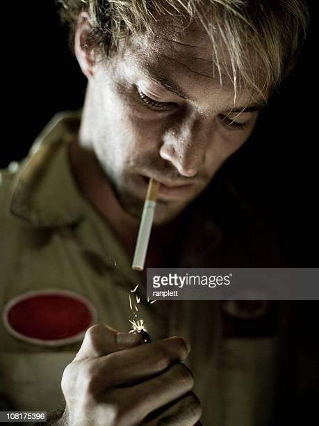 Auto Mechanic Lighting a Cigarette