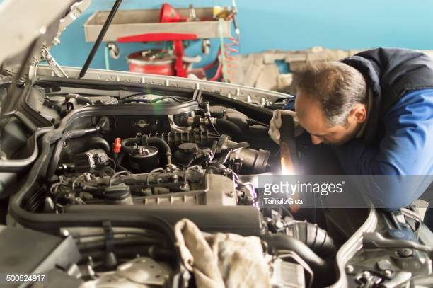 auto mechanic makes inspection and check a diesel engine car