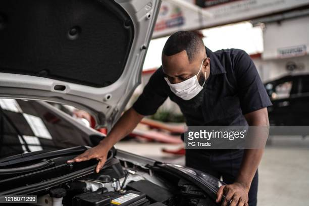 auto mechanic man with face mask working at auto repair shop - car repair stock pictures, royalty-free photos & images
