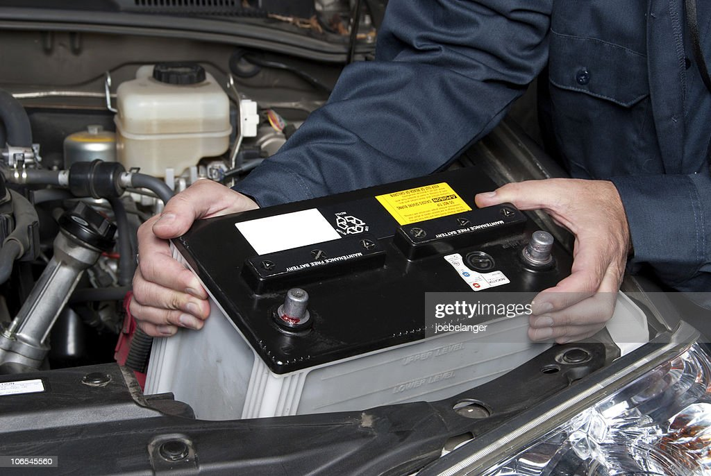 Auto mechanic replacing car battery : Stock Photo