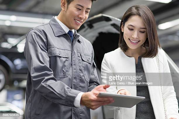 Auto mechanic talking with car owner