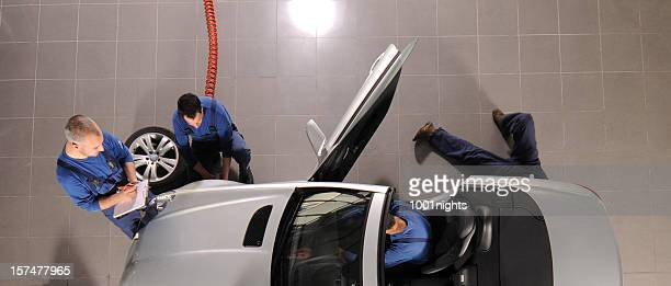 Auto mechanic team repairing the sports car