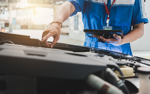 Auto mechanic uses the tablet to check. 1137474295