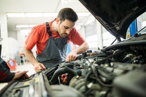 Auto mechanic working in garage. Repair service. 1073743202