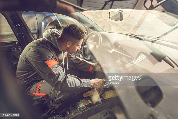 Auto mechanic working inside of a car in repair shop.