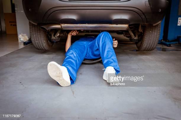 auto mechanic working on a car engine in repair shop. - sotto foto e immagini stock