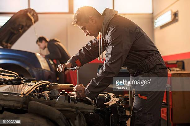 Auto mechanic working on a car engine in repair shop.