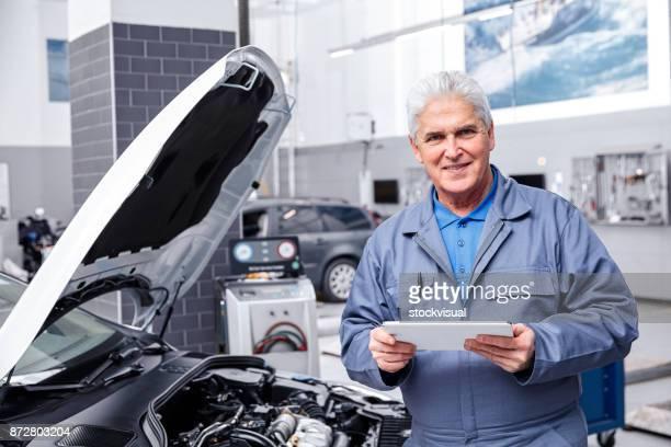 Mécanicien automobile travaillant sur un moteur de voiture réparation magasin.