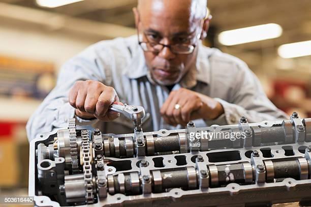 Auto mechanic working on gasoline engine