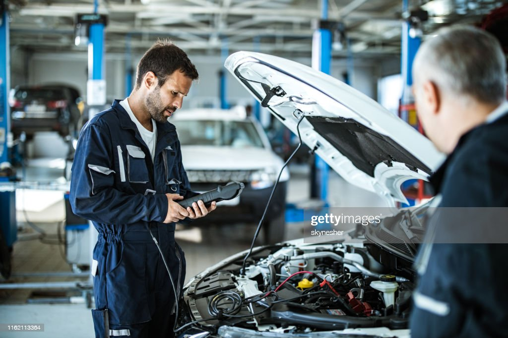 Auto mechanic working with car diagnostic tool in a repair shop. : Stock Photo