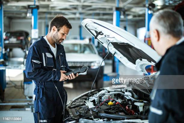auto mechanic working with car diagnostic tool in a repair shop. - mechanic stock pictures, royalty-free photos & images