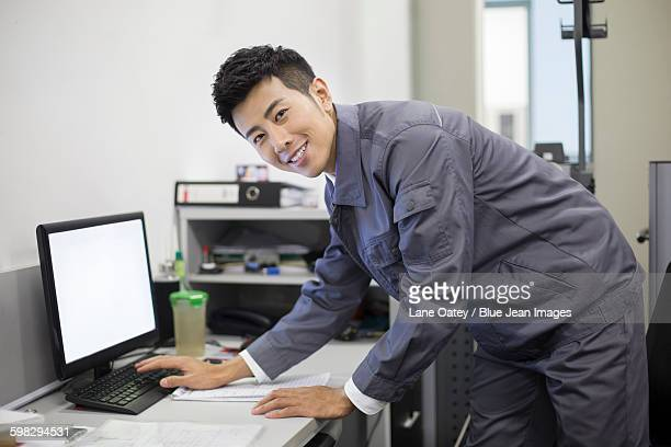 Auto mechanic working with computer