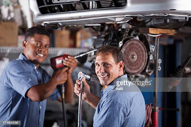 Auto mechanics in garage working on car transmission