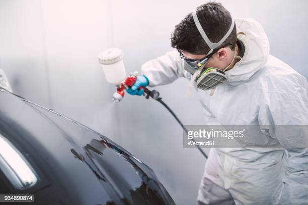 Auto painter painting a car inside a paint booth