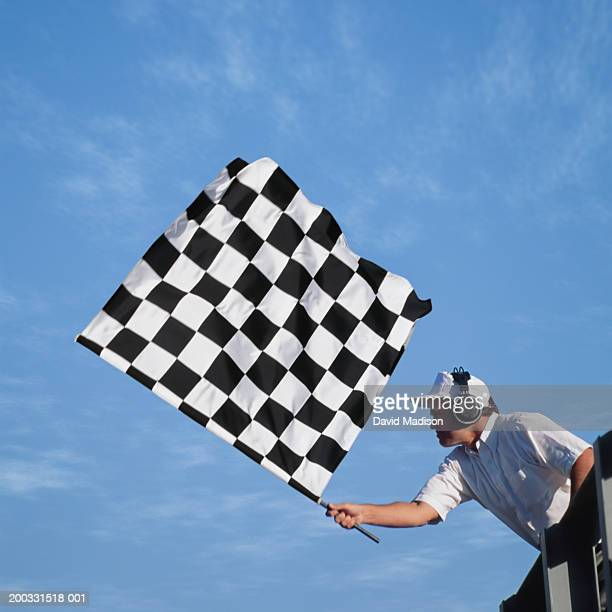 Auto race official waving checkered flag, low angle view