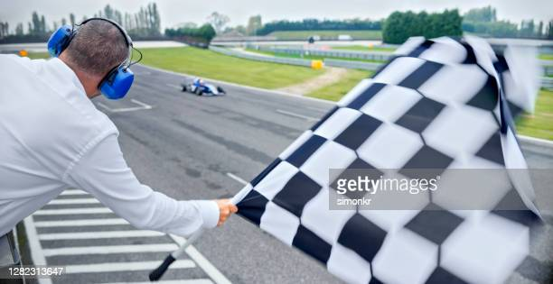 auto race official waving checkered flag - sports race stock pictures, royalty-free photos & images