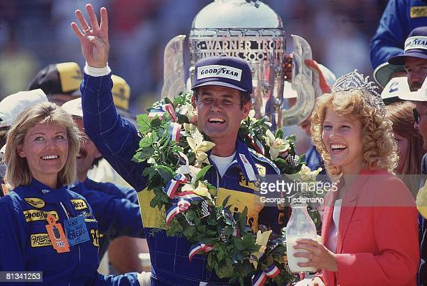 Auto Racing Indianapolis 500 Closeup of Al Unser Sr victorious with BorgWarner Trophy and gesturing number four with hand from Victory Lane after...