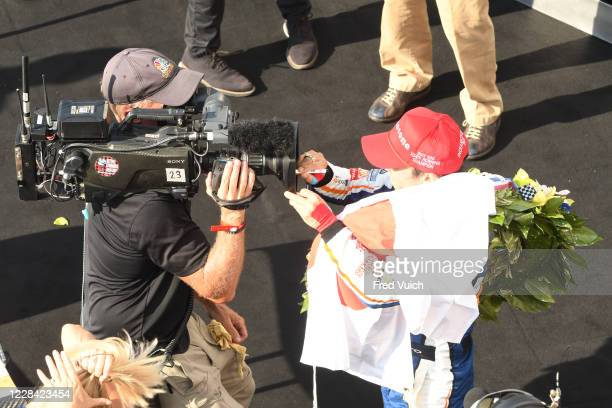 Indy 500: Aerial view of Takuma Sato signing autographs on television camera lens after winning race at Indianapolis Motor Speedway. Indianapolis, IN...