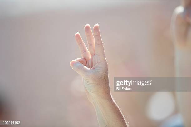 NASCAR Daytona 500 Closeup of fans holding up three fingers during memorial for late driver of car Dale Earnhardt Sr before race at Daytona...