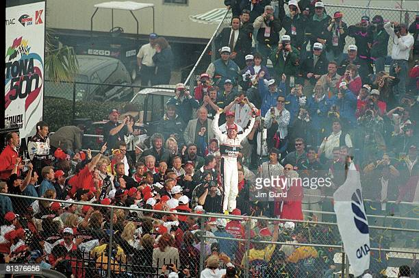 Auto Racing NASCAR Daytona 500 Dale Earnhardt Sr victorious standing on top of car in victory lane after winning race Daytona FL 2/15/1998
