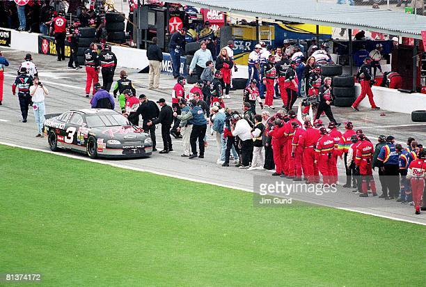 Auto Racing NASCAR Daytona 500 Dale Earnhardt victorious from line of pit crews after winning race Daytona FL 2/15/1998