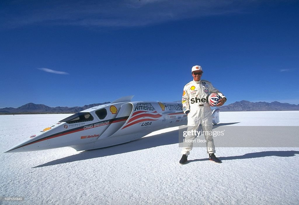 Portrait of Craig Breedlove with turbojet powered Spirit of America Formula Shell LSRV vehicle during photo shoot at Bonneville Speedway. Land speed record attempt. Bonneville Salt Flats, UT 9/25/1996