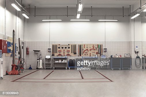 Auto Repair Shop Interior With Mechanic In Background High