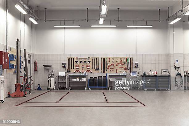 auto repair shop interior with mechanic in background - auto repair shop stock pictures, royalty-free photos & images