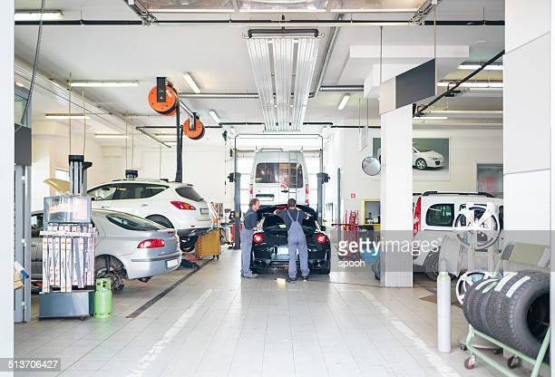auto repair shop with car serviced by mechanics - werkplaats stockfoto's en -beelden