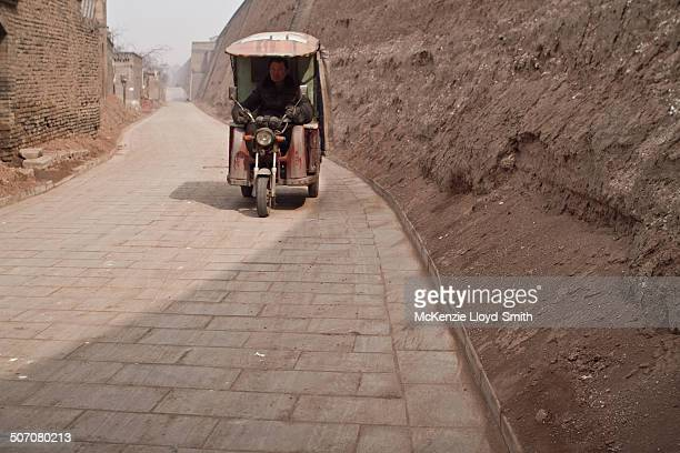 Auto rickshaw, known as a three-wheeler, tempo, tuk-tuk, trishaw, autorick, rick, tricycle, mototaxi, baby taxi or lapa - drives along cobbled street...