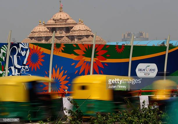 Auto rickshaws travel along the highway past Commonwealth Games Delhi 2010 signs in front of the Akshardham Swaminarayan Temple near to the athletes'...