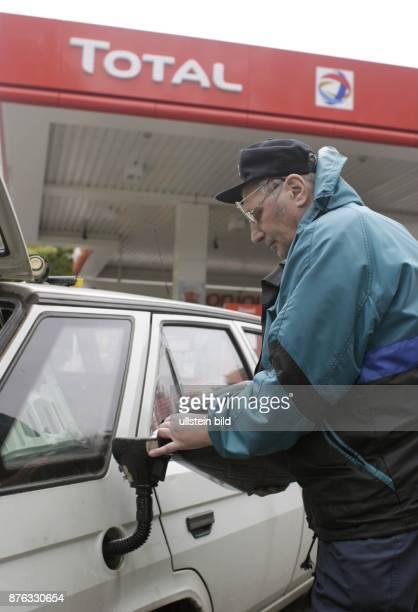 Autofahrer füllt aus einem Reservekanister Benzin in den Tank seines Autos NurfürredaktionelleZwecke